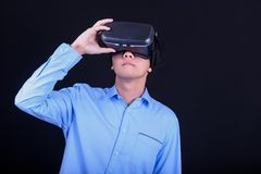 Young Asian man wearing virtual reality goggles. With black background studio. Smartphone using with VR headset stock photos