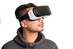 Young asian man wearing virtual reality goggles looking upwards. Half profile of young asian man wearing virtual reality goggles looking upwards, white stock image