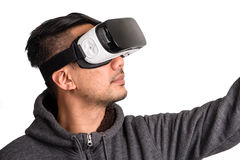 Young asian man wearing virtual reality goggles looking upwards. And pointing, white background stock image