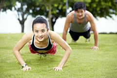 Young asian man and woman doing push-ups stock photos