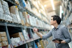 Asian man doing stocktaking by using tablet in warehouse. Young Asian man worker doing stocktaking of product in cardboard box on shelves in warehouse by using royalty free stock photography