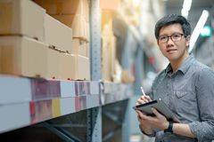 Asian man doing stocktaking by using tablet in warehouse. Young Asian man worker doing stocktaking of product in cardboard box on shelves in warehouse by using stock photos