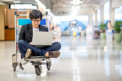 Young asian man working on airport trolley. With his laptop computer during waiting for a connecting flight, freelance lifestyle and digital nomad concepts Royalty Free Stock Photo