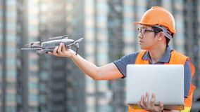 Asian man using drone and laptop for construction site survey. Young Asian man working with drone and laptop computer at construction site. Using unmanned aerial royalty free stock image