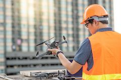 Asian man using drone and laptop for construction site survey. Young Asian man working with drone laptop and smartphone at construction site. Using unmanned stock image