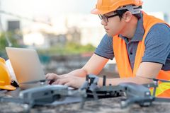 Asian man using drone and laptop for construction site survey. Young Asian man working with drone laptop and smartphone at construction site. Using unmanned stock photography
