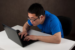 Young asian man working on his laptop computer Royalty Free Stock Photo