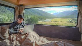 Young Asian man working with laptop in camper van. Young Asian man working with laptop computer on the bed in camper van with mountain scenic view through the royalty free stock photography