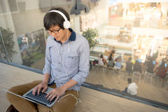 Young Asian man working with laptop while listening to music Royalty Free Stock Photography