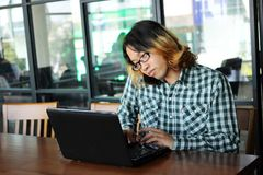 Young Asian man working with laptop and mobile smart phone in office. royalty free stock photo