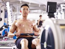 Young asian man working out using rowing machine. Young asian muscle man working out in gym using rowing machine Stock Photos