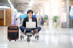 Young asian man working on trolley in airport terminal Stock Image