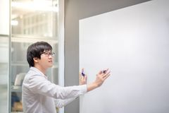 Young Asian man writing on white board in meeting room. Young Asian man writing on white board in conference room. Business meeting presentation concept Stock Photography
