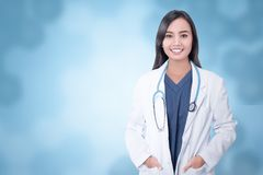Young asian medical doctor with hands in coat pocket. Over blue background royalty free stock images