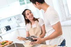 Young asian man and woman couple together making bakery cake and bread stock photography