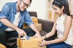 Young asian man and woman taping up a cardboard box in the office SME business stock photos
