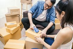 Young asian man and woman taping up a cardboard box in the office SME business stock image