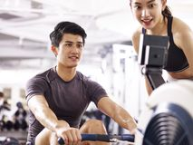 Young asian couple working out using rowing machine. Young asian men and women working out in fitness center using rowing machine Stock Photos