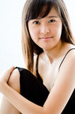 Young Asian Model. A young Asian woman wearing black dress on white background Royalty Free Stock Images