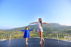 Young Asian mom and daughter feeling free with arms wide open at beautiful trees and mountains on blue sky.  royalty free stock image
