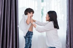 Young Asian mom dressed up son outfits for preparing go to school. Mother and son concept. Happy family and Home sweet home theme. Preschool and Back to school stock images