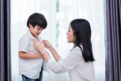 Young Asian mom dressed up son outfits for preparing go to school. Mother and son concept. Happy family and Home sweet home theme stock photos
