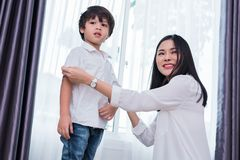 Young Asian mom dressed up son outfits for preparing go to school. Mother and son concept. Happy family and Home sweet home theme. Preschool and Back to school stock photos