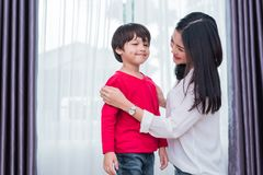 Young Asian mom dressed up son shirt for preparing go to school. Mother and son concept. Happy family and Home sweet home theme. royalty free stock photo