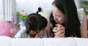 Young Asian Mother and child kissing and hugging, Resting on bed together
