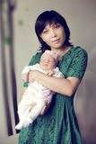 Young Asian mother in a green dress holding a newborn baby Royalty Free Stock Photography