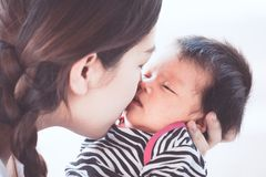 Young asian mother hugging and kissing her newborn baby girl. With love in vintage color tone Stock Photos