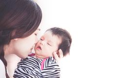 Young asian mother hugging and kissing her newborn baby girl. With love in vintage color tone Royalty Free Stock Photo
