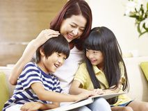Asian mother reading story to two children. Young asian mother sitting on couch at home reading story to two little children stock images