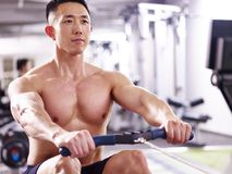 Young asian man working out using rowing machine Stock Photography