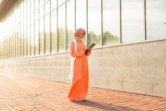 Young asian muslim business woman smiling and holding file document Royalty Free Stock Image