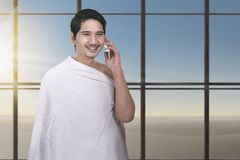 Young asian muslim man with ihram cloth using cellphone royalty free stock photography