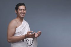 Young asian muslim man in ihram holding prayer beads Stock Images