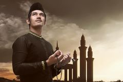 Young asian muslim man pray with prayer beads. With sunset background Stock Photos