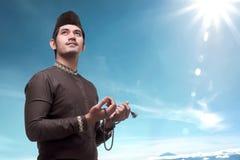 Young asian muslim man with prayer beads pray to god Royalty Free Stock Photos