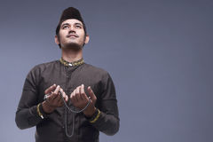 Young asian muslim man praying with prayer beads Royalty Free Stock Image