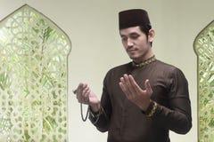 Young asian muslim man praying with prayer beads Stock Photography