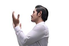 Young asian muslim man raising hand and praying Stock Images