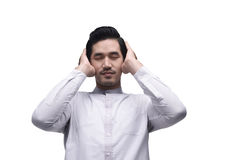 Young asian muslim man in traditional dress praying Stock Photography