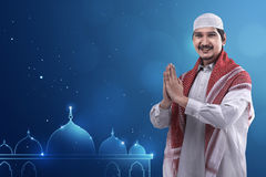 Young asian muslim man wearing cap and neat dress and mosque log Royalty Free Stock Images