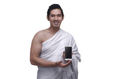 Young asian muslim man wearing ihram dress holding phone Stock Images