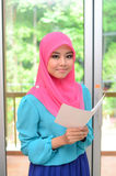 Young asian muslim woman in head scarf smile with holding card Stock Photos