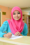 Young asian muslim woman in head scarf smile while holding pen Stock Image