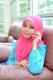 Young asian muslim woman in head scarf smile with mobile phone Stock Photos