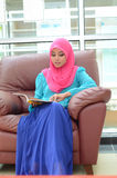 Young asian muslim woman in head scarf smile reading  magazine Royalty Free Stock Photography