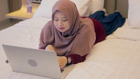 Young asian muslim woman laying down on bed using laptop stock video